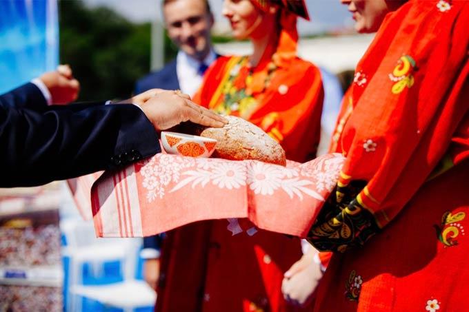 身着盛装的俄罗斯女孩招待宾客盐和面包